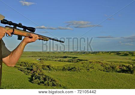 Hunter with rifle takes aim