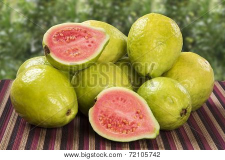 A basket full of brazilian guavas over a wooden surface.