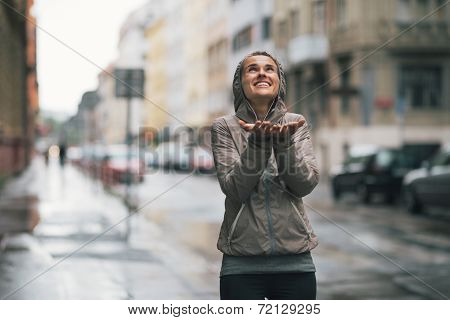 Happy Fitness Young Woman Catching Rain Drops In The City