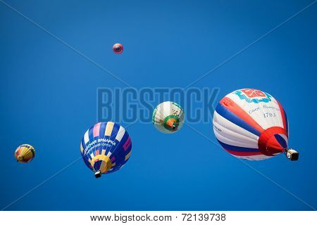 Bright colored balloons in blue sky
