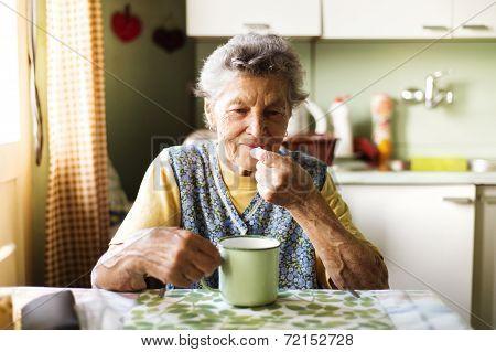 Old woman taking pills