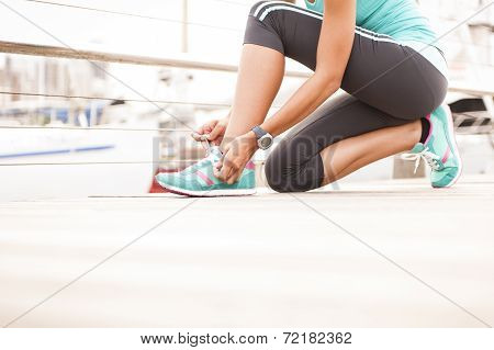 Young girl tying her shoe laces before enjoying a morning run