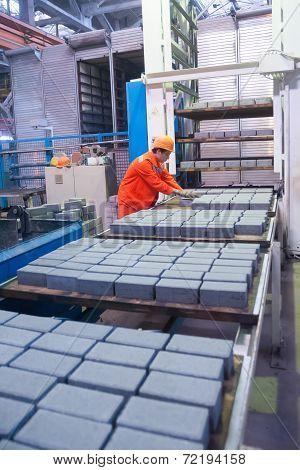 Worker at machine on stone blocks drying