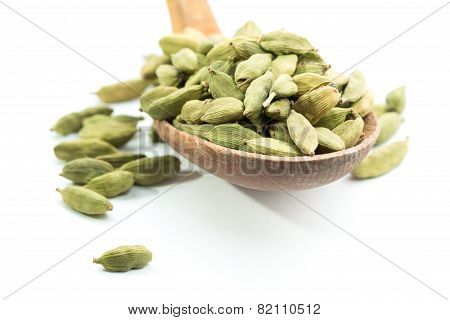 Lots of cardamom pods on wooden spoon. Isolated. White background. poster