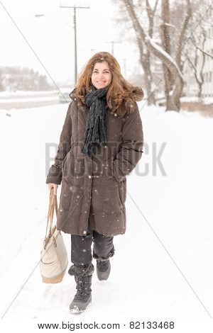 Middle Age Woman Walking In A City During A Snowfall