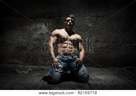 Muscular shirtless young man on his knees with light above head