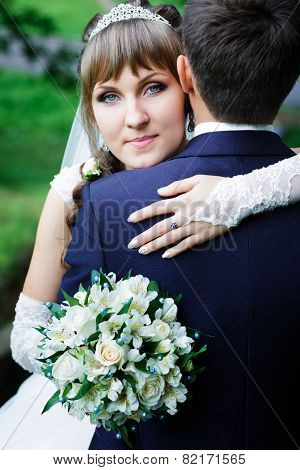 Bride hugging groom.