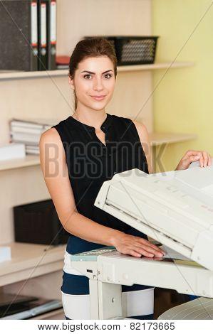 Pretty young secretary using a copy machine