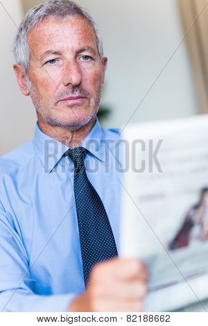 Successful mature handsome businessman reading the newspaper