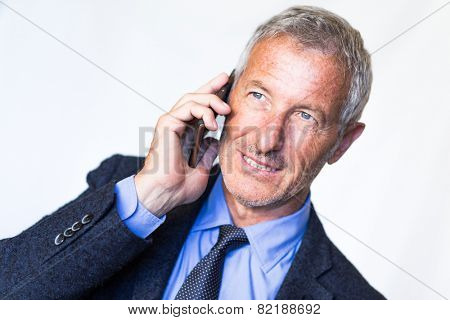 Successful mature handsome businessman using his smart phone for a job call. Communictaion and technology theme