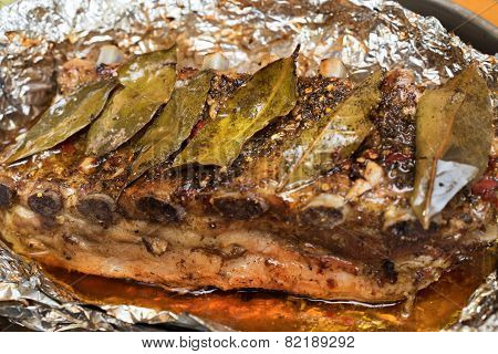 Barbecued Grilled Ribs Seasoned With Hot Spices And Laurel Leaves Laying On A Folio Close Up