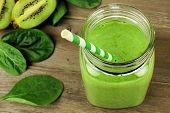 Healthy green smoothie with spinach and kiwi in a jar mug on wood downward view poster