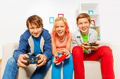Happy teens holding joysticks and playing game console sitting on the sofa at home poster