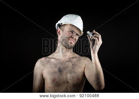 Happy dirty worker in helmet. gemstone,