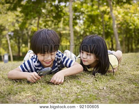 Asian Children Playing With Magnifier Outdoors
