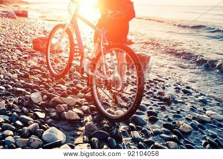 Man with bicycle on a sea shore sunset