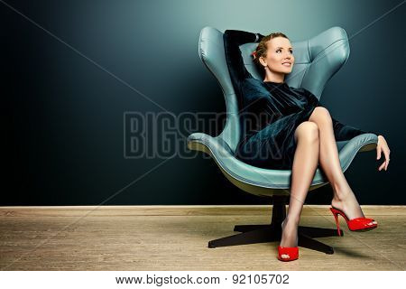 Portrait of a stunning fashionable model sitting in a chair in Art Nouveau style. Business, elegant businesswoman. Interior, furniture. poster