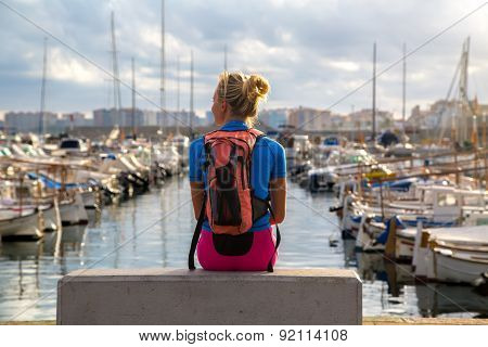 Young Woman Sitting  In The Harbor.