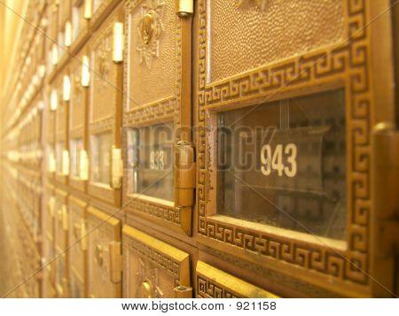 a wall of golden post office boxes. poster