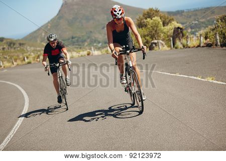 Cyclist riding bikes on open road. Triathletes cycling down the hill on bicycles. Practicing for triathlon race on country road. poster