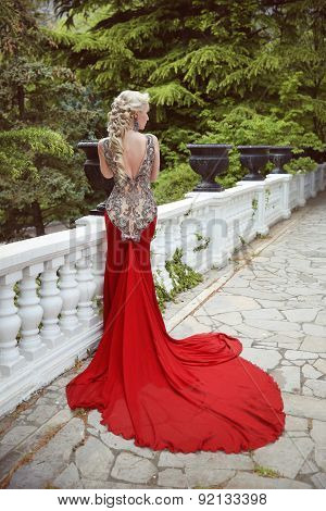 Fashion Elegant Blond Woman Model In Red Gown With Long Train Of Dress. Outdoor Full Length Portrait