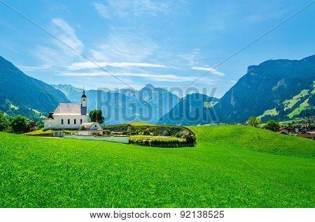 Alpine landscape with typical church Austrian Alps