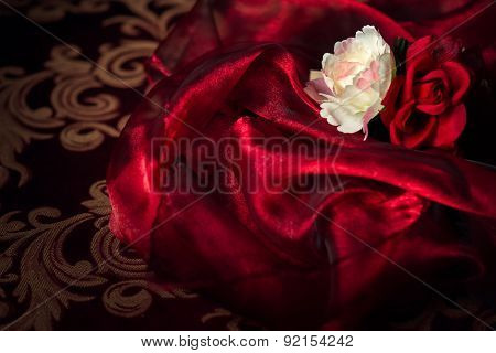 Two Silk Flowers On Red Silk Material Background