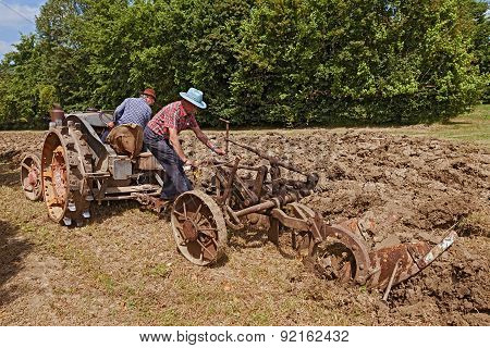 Farmers Plowing With An Old Tractor