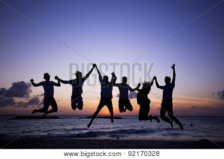 Group of young people at the beach at dusk. Silhouette group.
