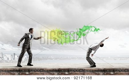Young businessman trying to evade from thrown splashes