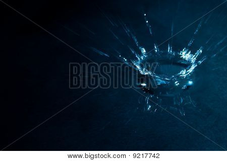 A blue coloured splash of water on a dark background. The water is very shallow and you can see the reflection of the splash. poster