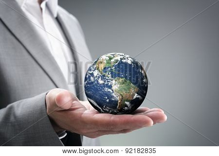 Businessman holding the world in the palm of hands concept for global business, communications, politics or environmental conservation  Earth image courtesy of Nasa at http://visibleearth.nasa.gov