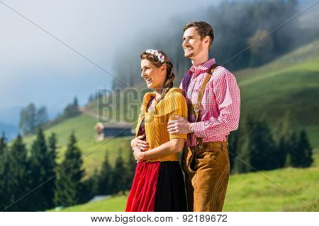 Couple in Tracht on Alp mountain summit at vacation