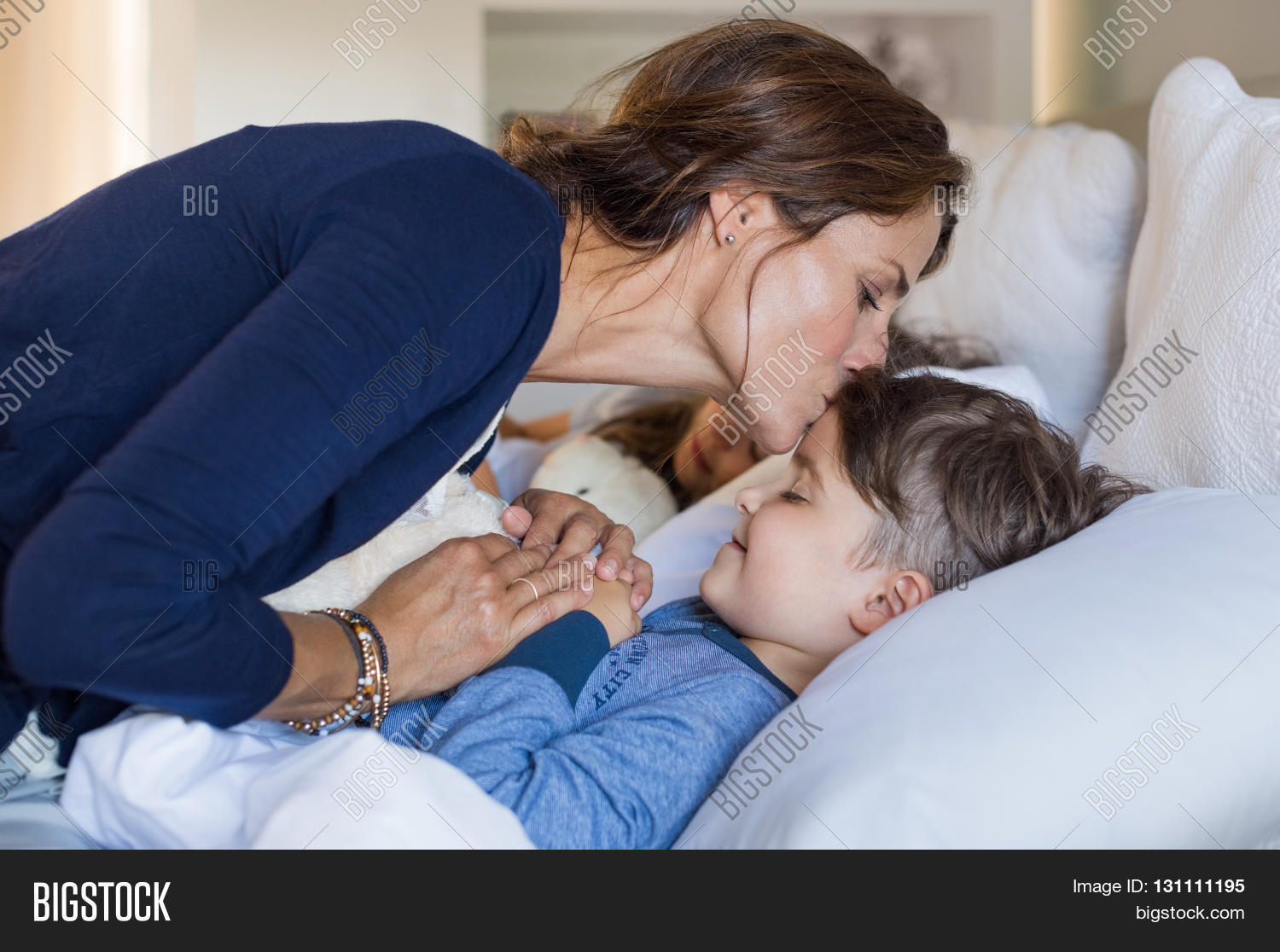 Mother Giving Good Night Kiss To Sleeping Son Lovely Putting Bed