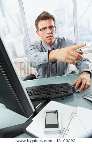Ernst Kaufmann im Gespräch über Festnetz Telefon Gestikulieren aus Bild am Schreibtisch sitzen.