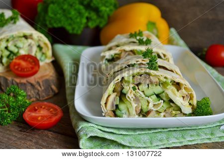 roll pita with chicken mushrooms and vegetables on a wooden background