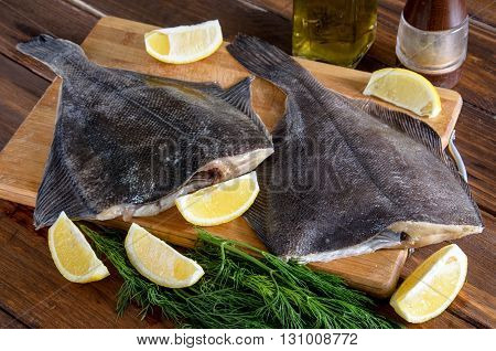 Raw fish flounder, flatfish on wooden table