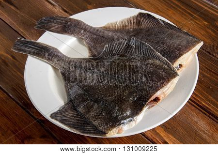 Raw fish flounder, flatfish on wooden table