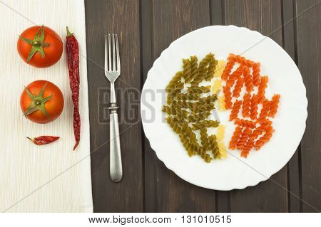Three Colors Rotini Pasta on a plate. Colored pasta on the kitchen table. Advertising on pasta.