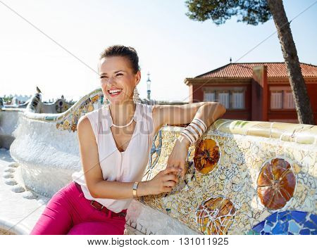 Smiling Woman Sitting On The Famous Trencadis Style Bench