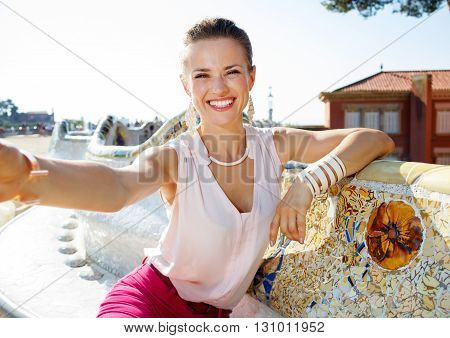 Happy Woman Taking Selfie On Famous Trencadis Style Bench