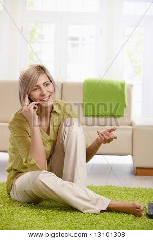 Cheerful woman speaking on mobile phone, sitting on living room floor, gesturing with hand.