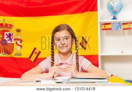 Cute schoolgirl with plaits, holding two Spanish flags in her hands, sitting at the desk