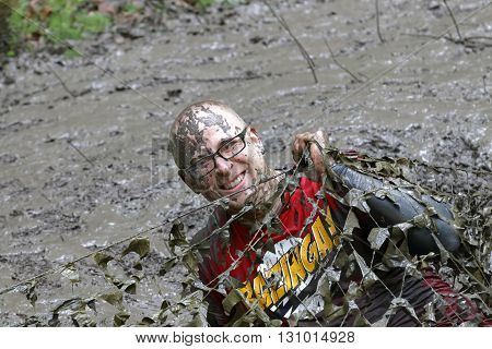 STOCKHOLM SWEDEN - MAY 14 2016: Smiling man covered with mud crawling under a camouflage net in the obstacle race Tough Viking Event in Sweden April 14 2016