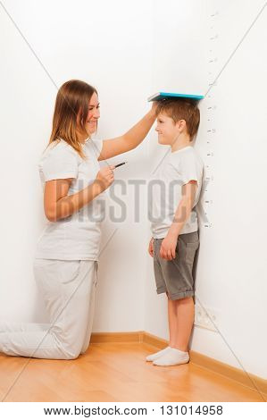 Mother checking her son's height on growth chart, as kid standing near the white wall, by using a book and a pen