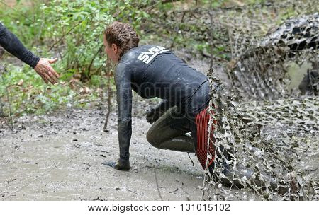 STOCKHOLM SWEDEN - MAY 14 2016: Woman covered with mud crawling under a camouflage net gets a helping hand in the obstacle race Tough Viking Event in Sweden April 14 2016