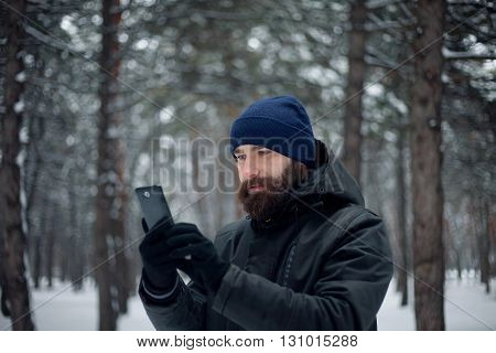 Portrait of a smiling young man in an ear flap hat with a snowball in his hand