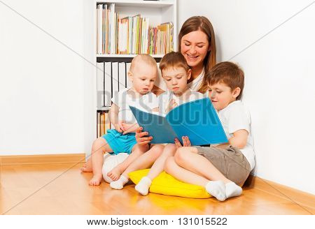 Young mother reading book to her three age-diverse kids, sitting on yellow pillow against white wall and bookshelf at the room