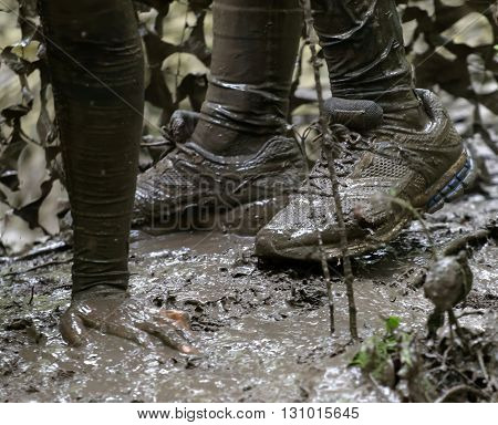 STOCKHOLM SWEDEN - MAY 14 2016: Shoes and a hand in the mud camo net in the background in the obstacle race Tough Viking Event in Sweden April 14 2016