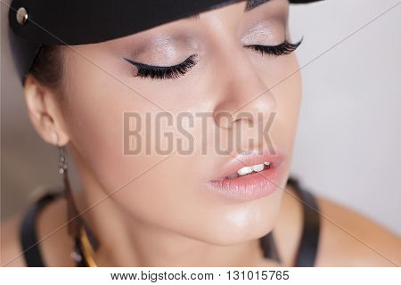 Close-up portrait of a beautiful sexy young woman in a leather visor and sword belt beauty portrait cropping photos